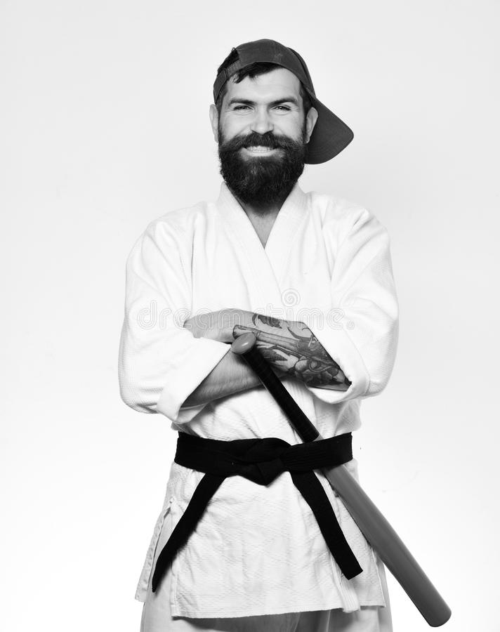 Karate man with smiling face puts green baseball bat behind black belt. Man with beard in white kimono and green cap. On white background. Martial arts concept royalty free stock image
