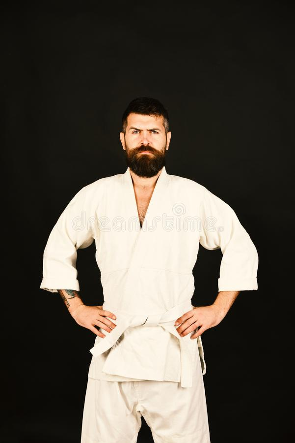 Karate man with strict face in uniform. Jiu Jitsu master. Poses holding hands on sides. Training and combat concept. Man with beard in white kimono on black stock photography