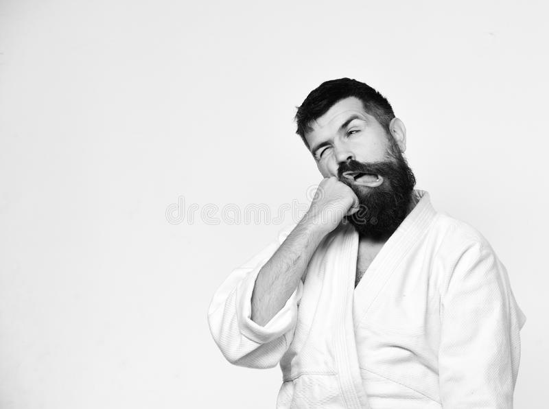 Karate man with suffering face in uniform. Japanese martial arts. Concept. Man with beard in white kimono on white background. Judo master hits himself with stock photography