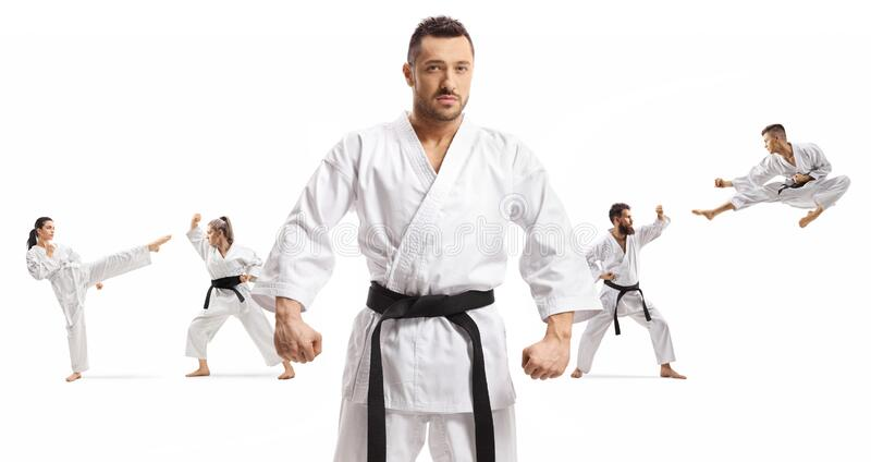 Karate master with black belt standing in front of men and women practicing martial arts stock photo