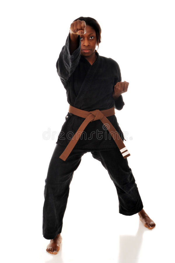 Karate Punch. African American woman throwing a punch during her karate kata. Isolated on white stock photography