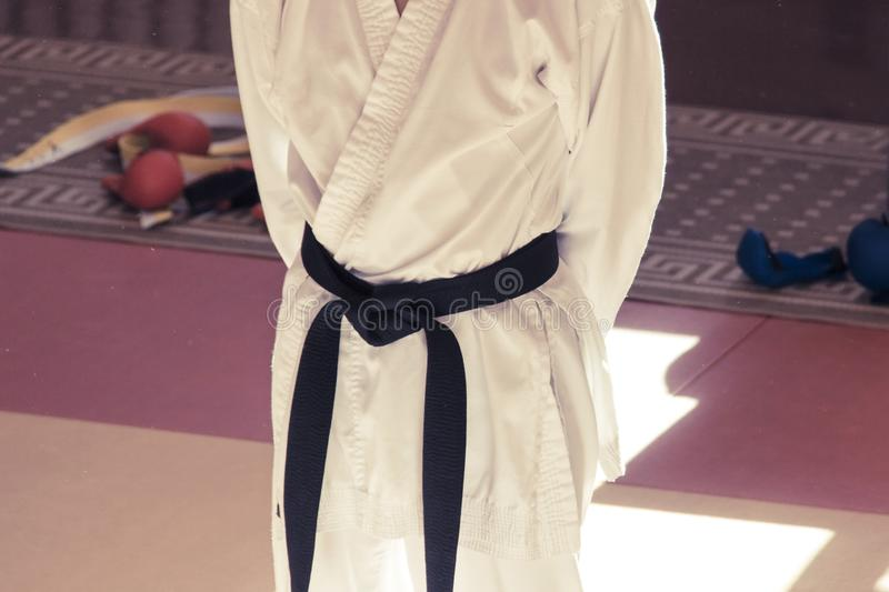 A karate trainer in a kimono with a black belt is in training at the gym royalty free stock image