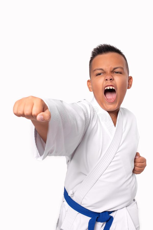 Karate young boy in white uniform makes a hit aggressively shouting, isolated. Karate young boy in white uniform makes a hit aggressively shouting against on royalty free stock photo