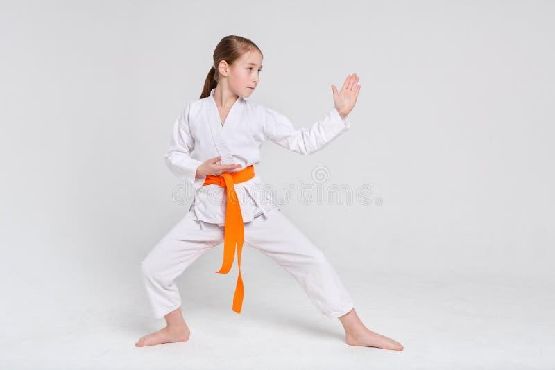 Karateflicka i kimono i ställning på studiobakgrund arkivbild