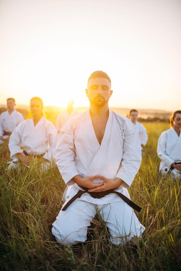 Karategruppsammanträde på jordningen och mediterar royaltyfri fotografi