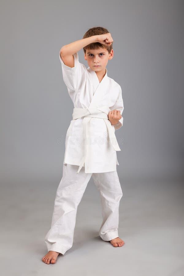 Karatejongen in het witte kimono vechten stock afbeeldingen