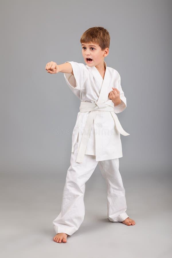 Karatejongen in het witte kimono vechten royalty-vrije stock afbeeldingen
