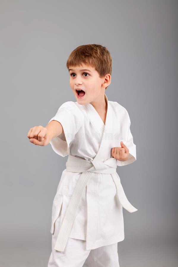 Karatejongen in het witte kimono vechten royalty-vrije stock afbeelding