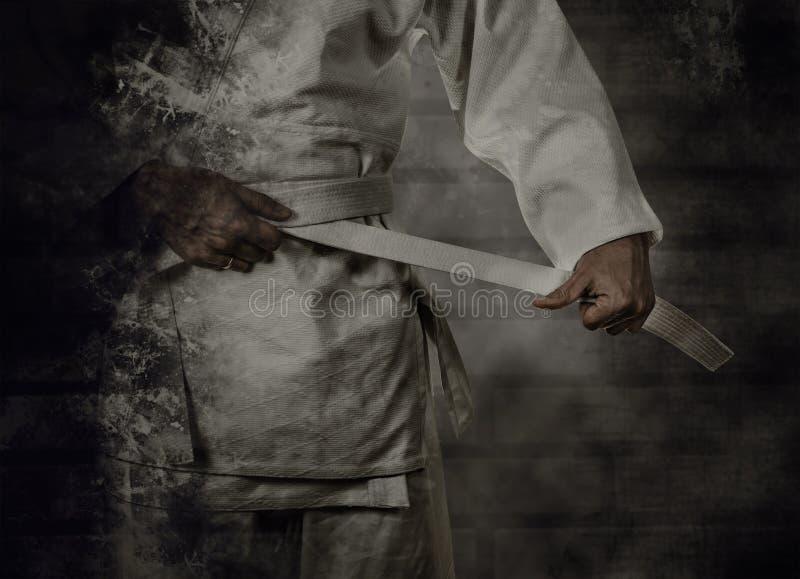 Karateka, das den weißen Gurt (Obi) bindet mit Schmutzhintergrund lizenzfreies stockfoto