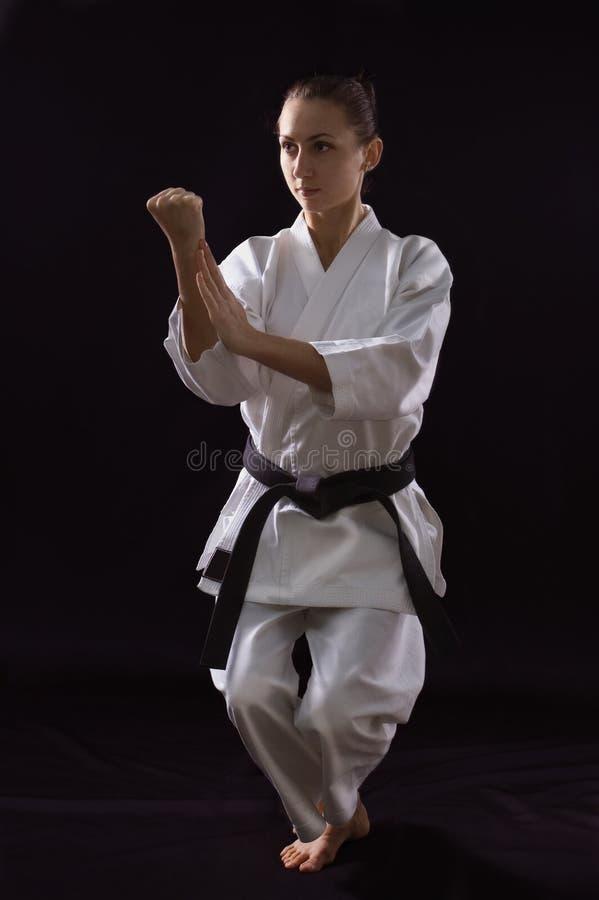 Karateka Mädchen auf schwarzem Hintergrund stockfotografie