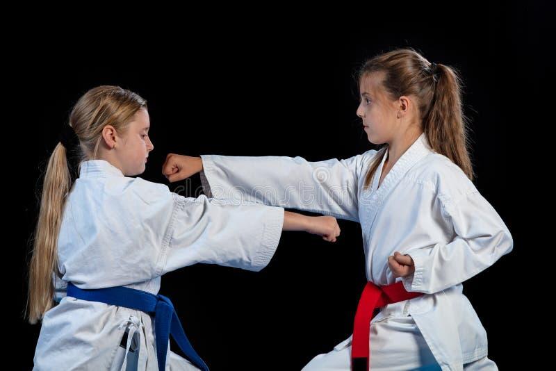 Karatekampfkünste zwei kleine Mädchen zeigen die Kampfkünste, die zusammenarbeiten lizenzfreies stockfoto