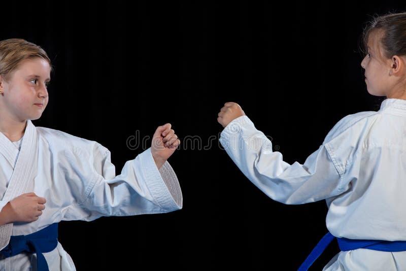 Karatekampsporter två små flickor visar kampsporter som tillsammans arbetar royaltyfri foto
