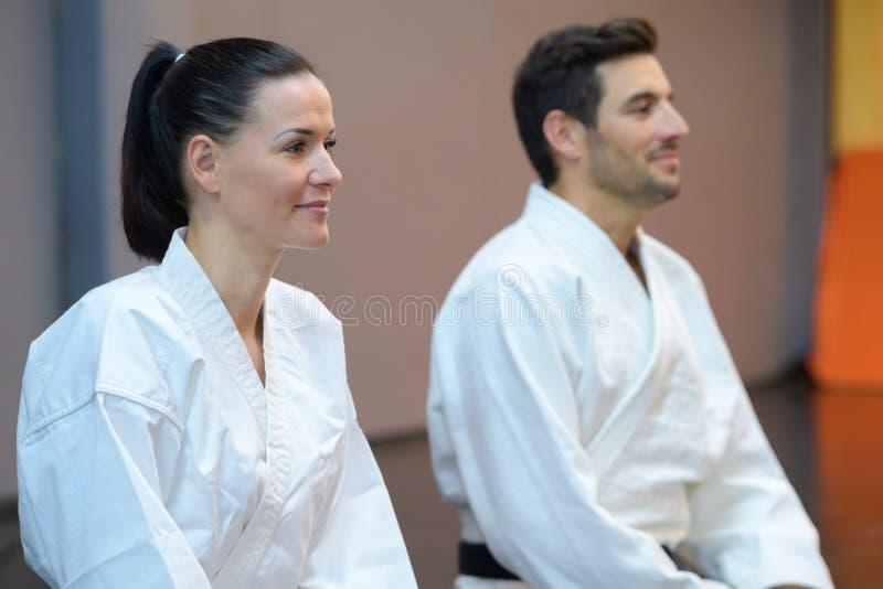 Karatekas femeninos y masculinos durante la lección fotos de archivo