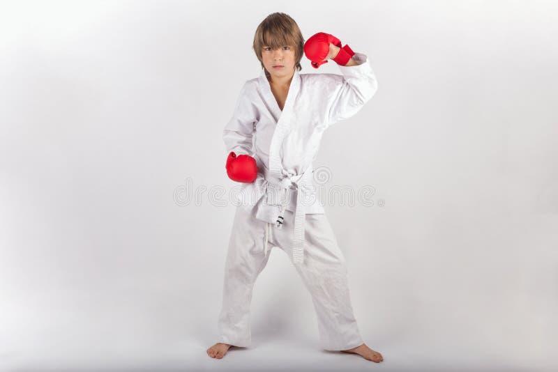 Karatekind mit der roten Boxhandschuhaufstellung lizenzfreie stockbilder
