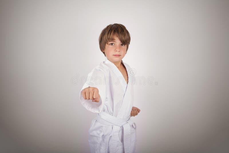 Karatekindertragende weiße Kimonoaufstellung stockfoto