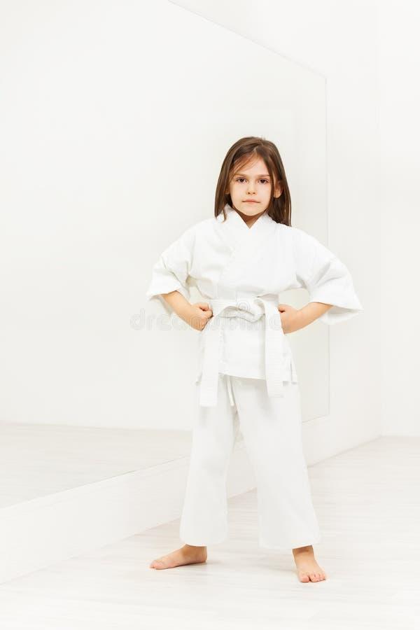 Karatemädchen, das mit den Händen auf Hüften in der Turnhalle steht stockfotografie