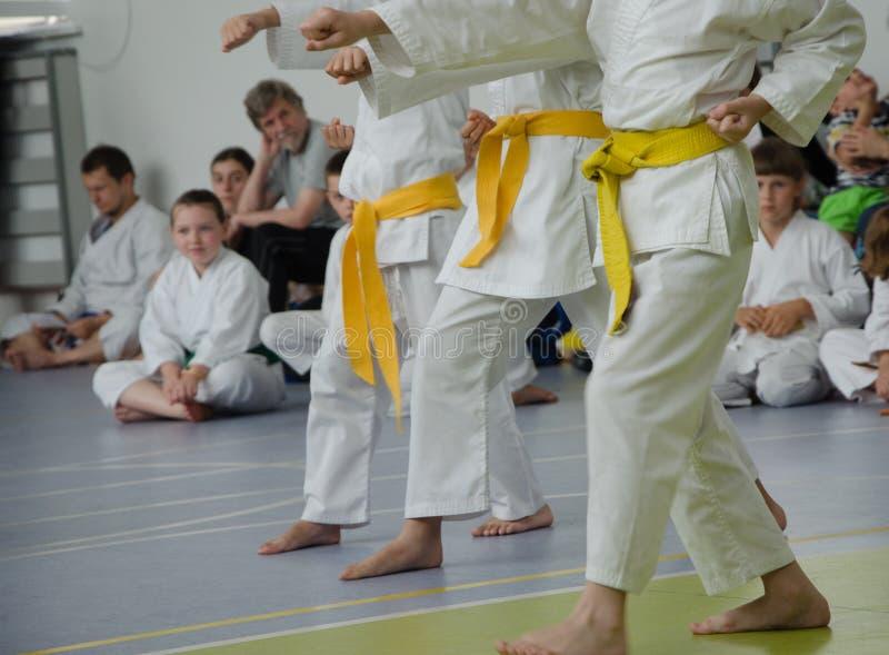 Karateutbildning Ungar av olika åldrar i kimono med guling är royaltyfria foton