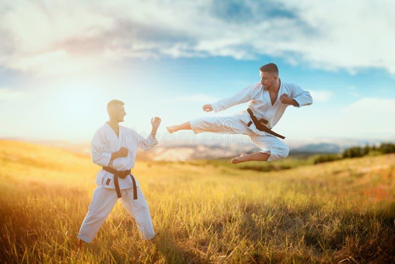 Karatevechters, schop tijdens de vlucht op opleidingsstrijd stock fotografie