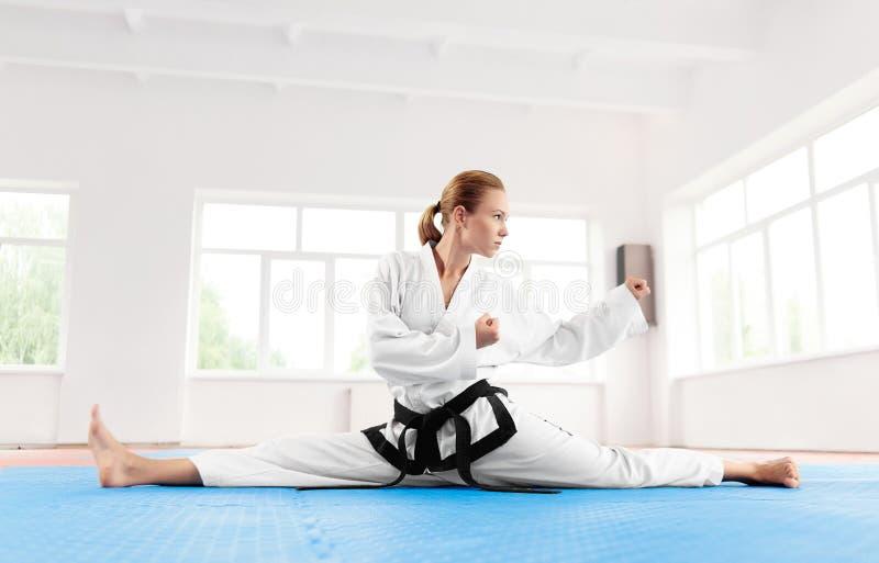Karatevrouw, die in kimono het uitrekken zich been vóór harde training dragen royalty-vrije stock foto's