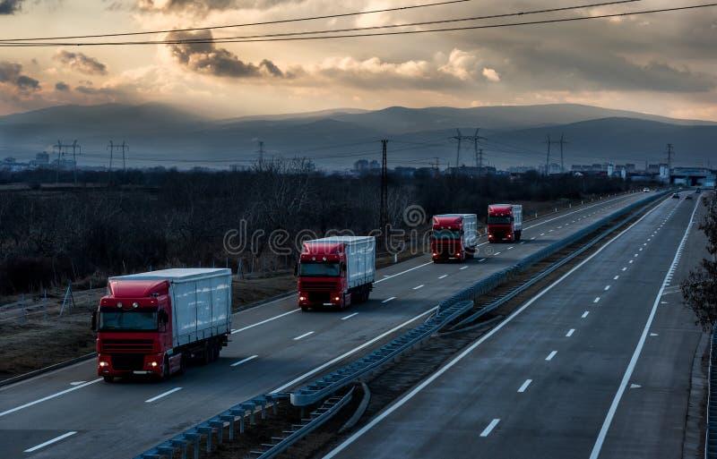 Karawana lub konwój ciężarówka przewozimy samochodem na kraj autostradzie zdjęcia royalty free
