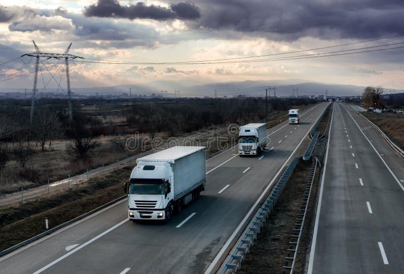 Karawany lub konwoju biała ciężarówka przewozi samochodem na kraj autostradzie obrazy royalty free