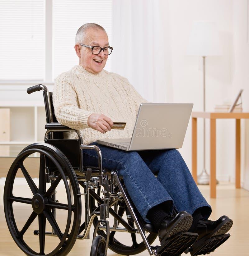 karciany kredyt obezwładniający mężczyzna używać wózek inwalidzki zdjęcie royalty free