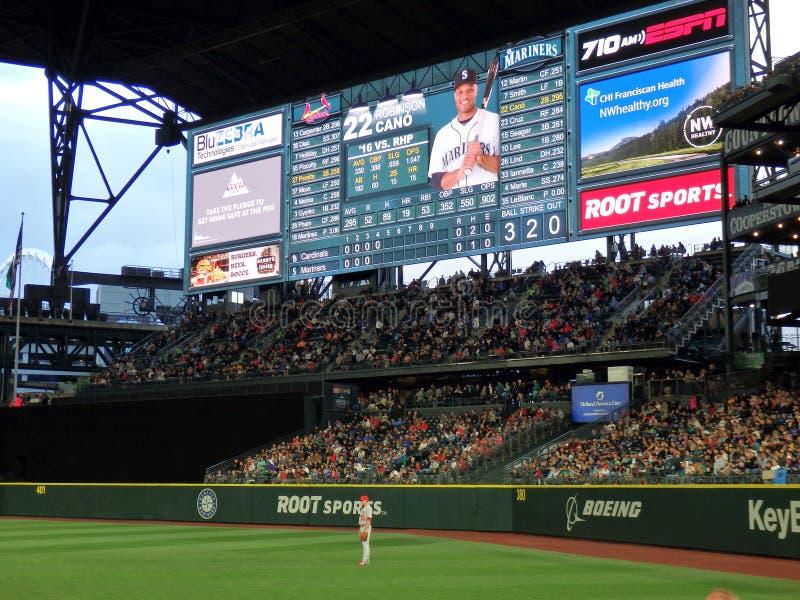 Kardinal-Spieler steht im Außenfeld mit Fans in Zuschauertribünen a lizenzfreie stockfotografie