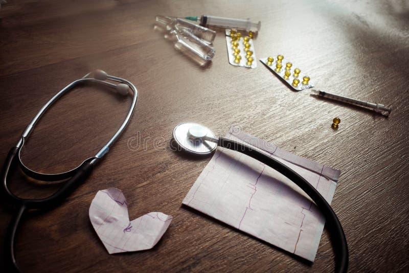 Kardiogram och stetoskop på den wood tabellen royaltyfria bilder