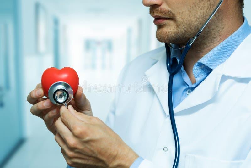 Kardiologe, der rotes Herz mit Stethoskop überprüft lizenzfreies stockfoto