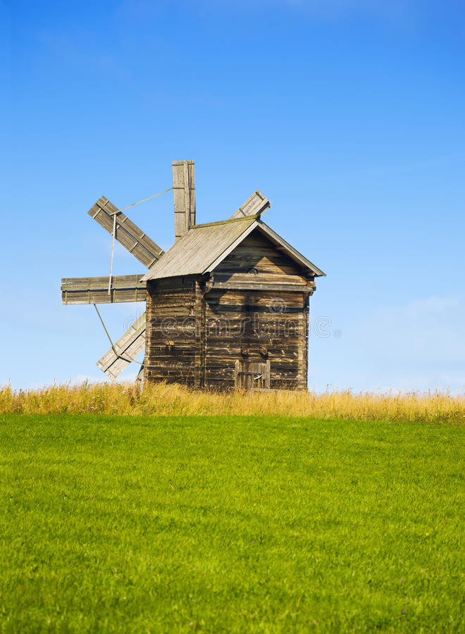 Karelia, Kizhi, Russia - August, 2015: Traditional wooden windmill on Kizhi Island. Wooden churches at background. Karelia, Russia stock photography