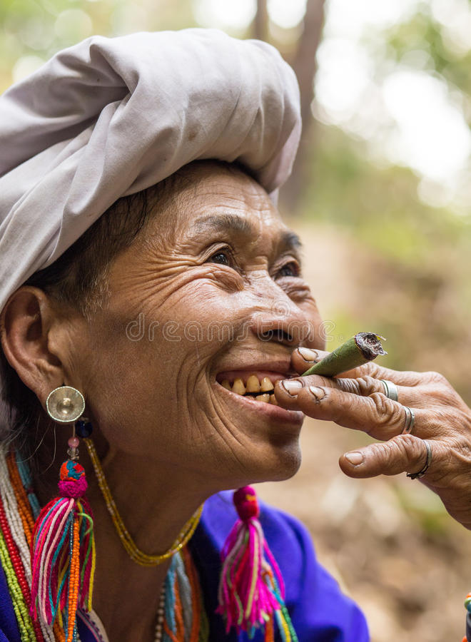 Karen tribe woman smoking cigarette. MAE KLANG LUANG, THAILAND - FEBRUARY 18, 2017 : A Karen hilltribe woman is smoking a large leaf cigarette in the Mae Klang stock photos