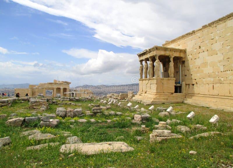 Kariatyd kolumny ganeczek Erechtheion starożytnego grka świątynia z Propylaea Monumentalną bramą w odległości, Grecja zdjęcie royalty free