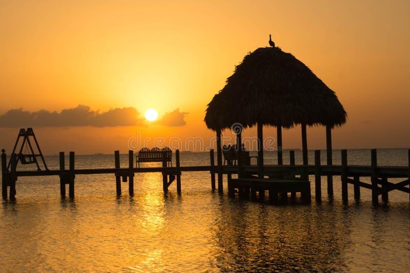 Karibischer Sonnenaufgang über Strohdachpier lizenzfreies stockbild