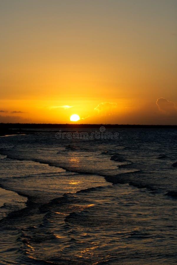 Karibischer Sonnenuntergang mit einem goldenen Himmel und kleinen Wellen lizenzfreies stockfoto