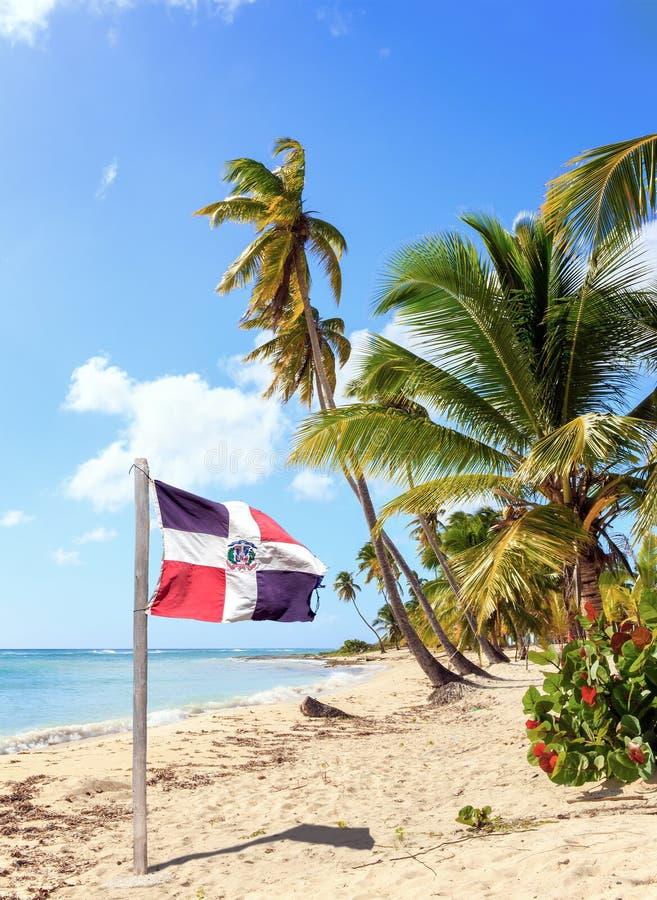 Karibisk strand och Dominikanska republikenflagga fotografering för bildbyråer