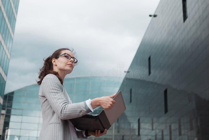 Kariera przyrost i ambicje, pojęcie Młody bizneswoman z laptopem na tle centrum biznesu zdjęcia royalty free