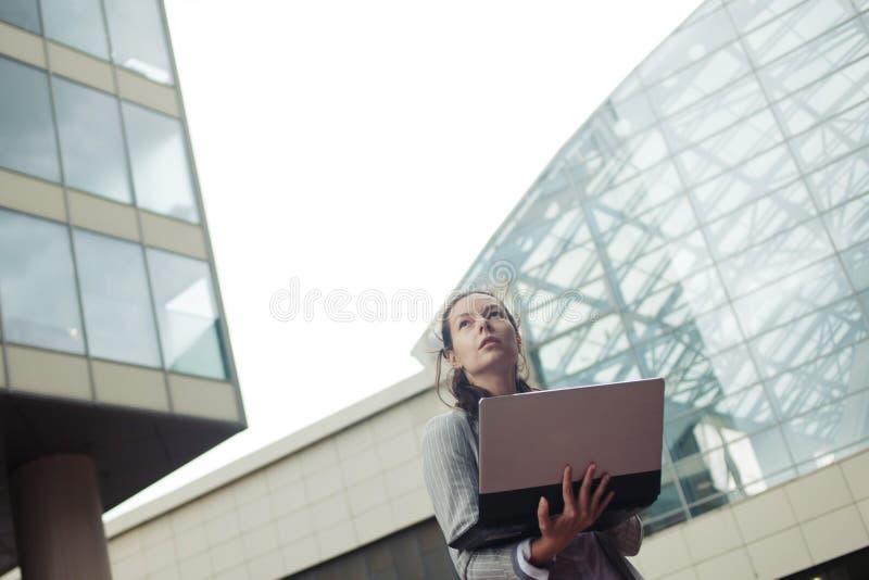 Kariera przyrost i ambicje, pojęcie Młody bizneswoman z laptopem w jej rękach na tle centrum biznesu fotografia stock