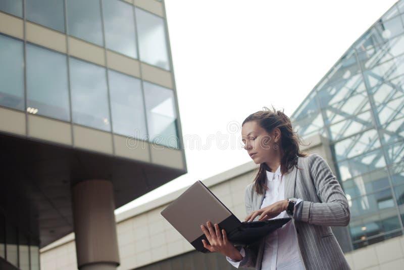 Kariera przyrost i ambicje, pojęcie Młody bizneswoman z laptopem w jej rękach na tle centrum biznesu obrazy royalty free