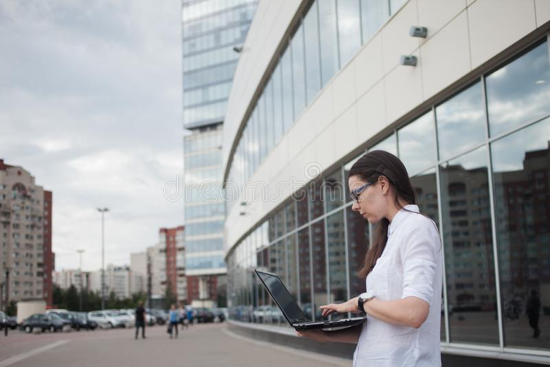 Kariera przyrost i ambicje, pojęcie Młody bizneswoman z laptopem w jej rękach na tle centrum biznesu zdjęcie stock