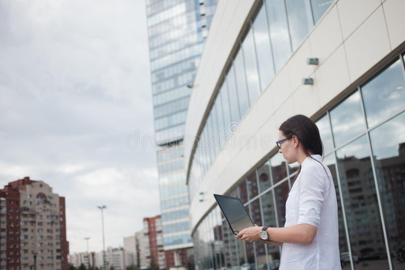 Kariera przyrost i ambicje, pojęcie Młody bizneswoman z laptopem w jej rękach na tle centrum biznesu obraz royalty free