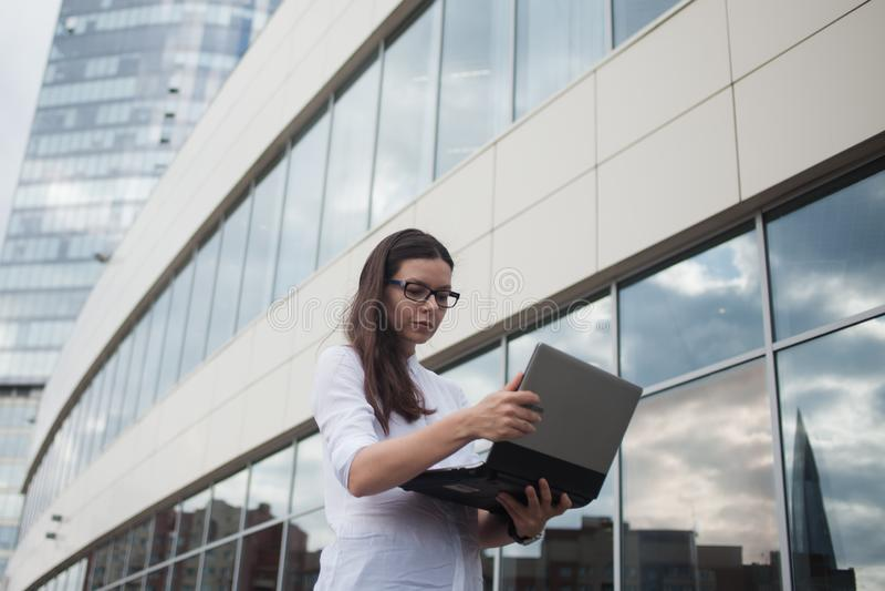 Kariera przyrost i ambicje, pojęcie Młody bizneswoman z laptopon tło centrum biznesu obraz royalty free