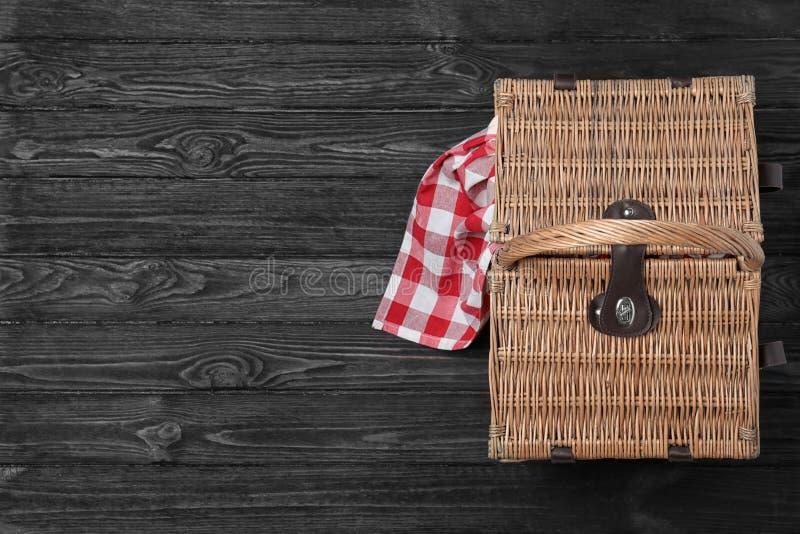 Karierte Tischdecke und geschlossener Weidenpicknickkorb auf schwarzem Holztisch, Draufsicht lizenzfreies stockfoto
