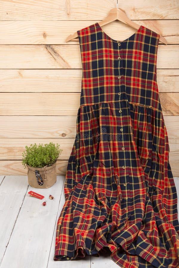 kariertes Kleid hängt an am Aufhänger und am Schmuck: Haarspange, Ohrringe auf hölzernem Hintergrund Vertikales Foto stockbilder