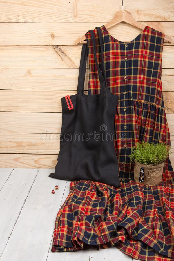 kariertes Kleid h?ngt an am Aufh?nger, an schwarzer eco Einkaufstasche und an der Haarspange auf h?lzernem Hintergrund Vertikales stockfotos