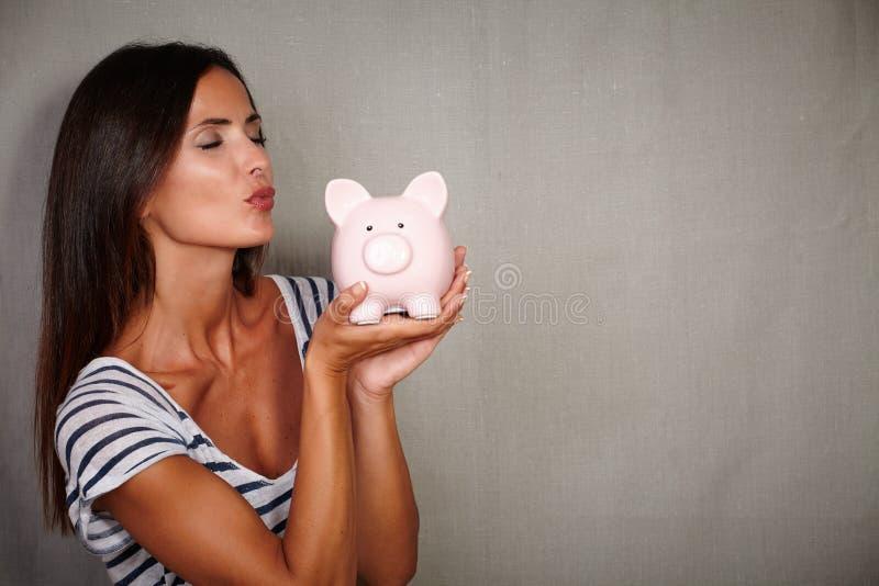 Karismatisk ung kvinna som kysser en spargris royaltyfria foton