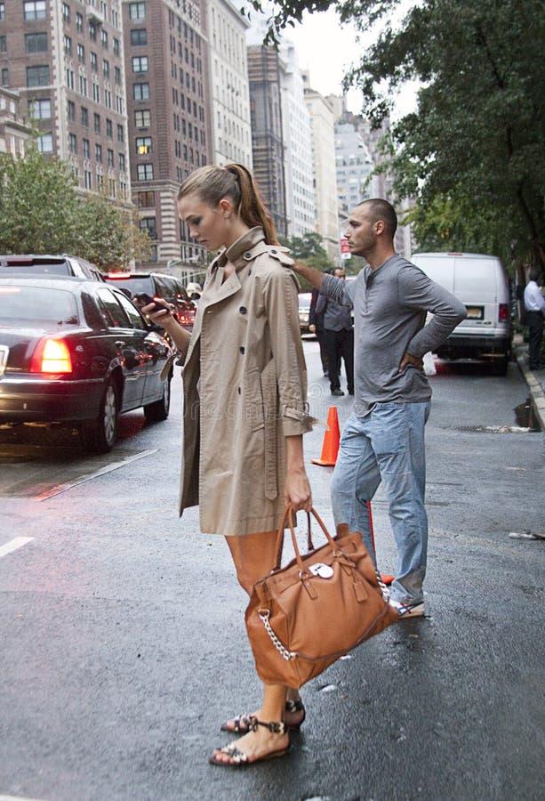 Karlie Kloss que mira su teléfono móvil en Manhattan New York City foto de archivo