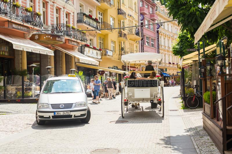 KARLOVY VARY, CZECH REPUBLIC - JUNE 12, 2017: A horse-drawn carriage awaits tourists on the embankment of the Tepla stock photography