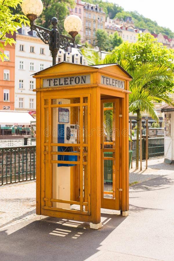 KARLOVY VARY, CZECH REPUBLIC - JUNE 12, 2017: Vintage telephone booth on the waterfront of the river Tepla. stock images