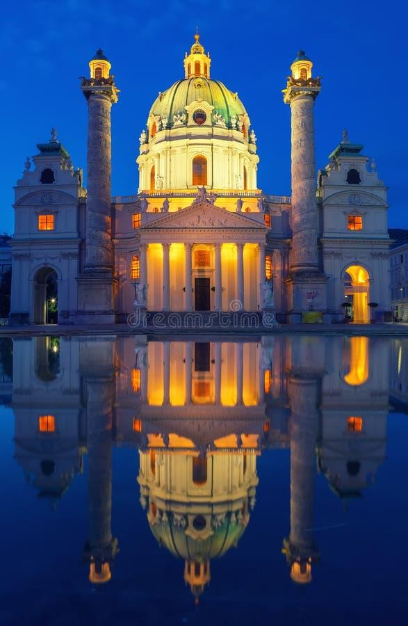 Karlskirche令人惊讶的看法与照明和反射在水中,维也纳,奥地利的 免版税库存图片