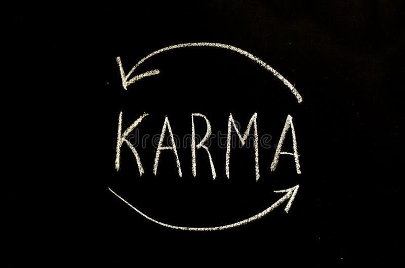 Karma και βέλη που γράφονται στον πίνακα κιμωλίας στοκ εικόνες